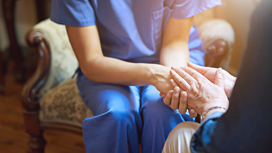 Nurse holding senior citizen's hand