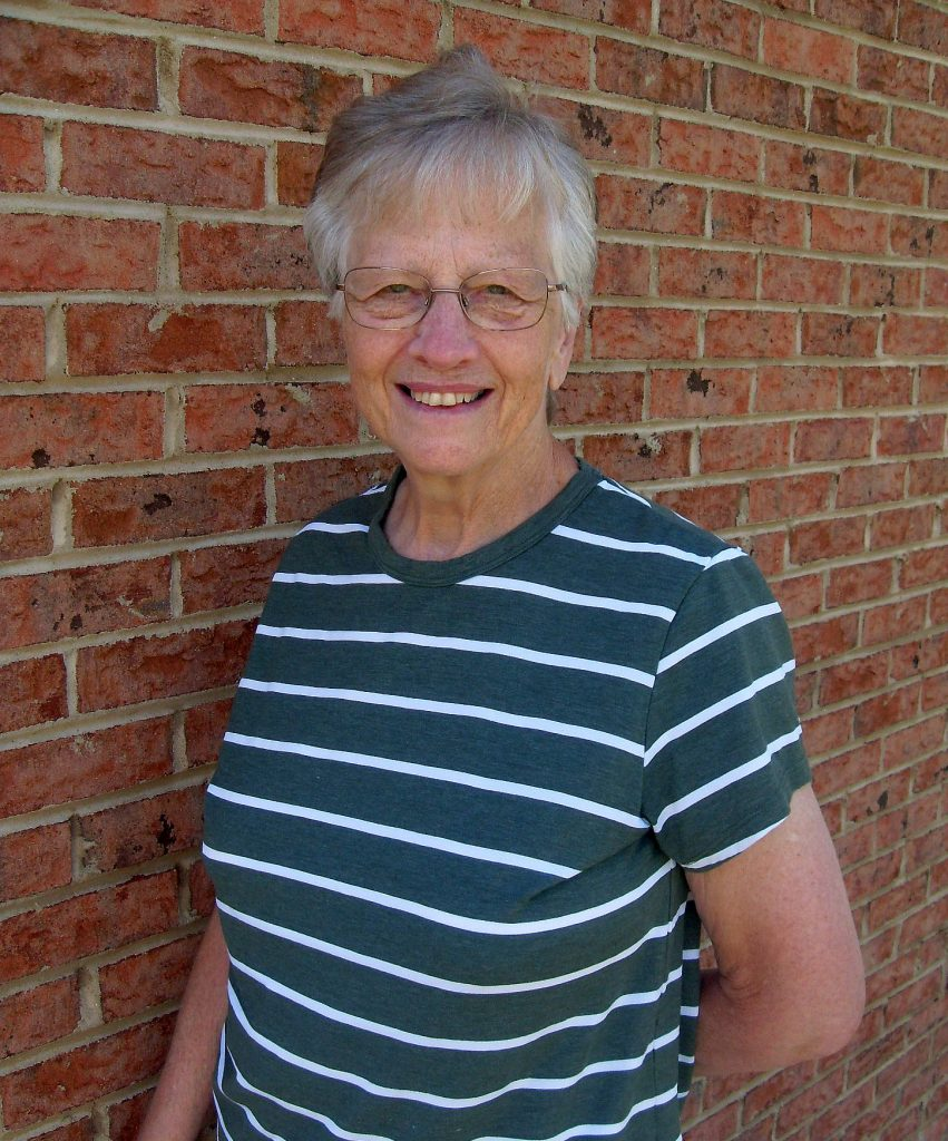 Mary Lee, retired LeConte employee, smiles in front of brick wall